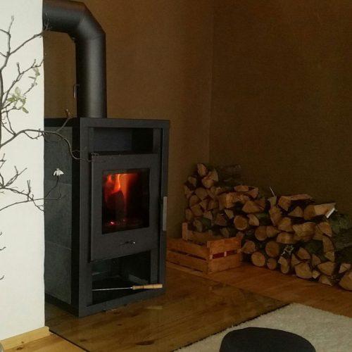 Der wärmende Kamin steht mitten im großen Yogaraum, perfekt für den Winter